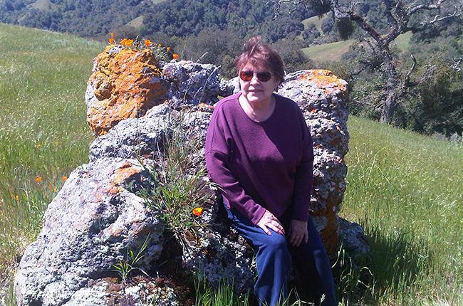 Blanca Alvarado sitting on flower-covered hillside
